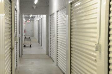 Clean indoor hallway of storage units with white doors