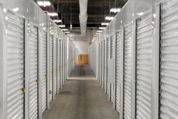 Well-lit, indoor hallway of white storage units