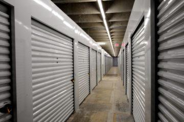 Clean, indoor hallway of white storage units
