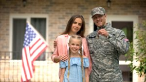 military family holding the key to a new house after they've moved